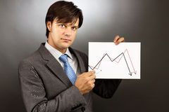 Businessman drawing a falling graph of stock market. Against gray royalty free stock image