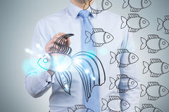 Businessman drawing fish sketch Stock Image