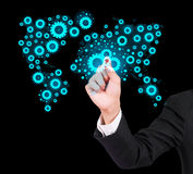 Businessman drawing gears. On black background, map world Stock Image