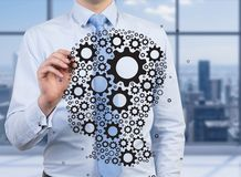 Businessman drawing gears. In form head, close up Royalty Free Stock Photography