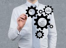 Businessman drawing gears. On a gray background Stock Photo