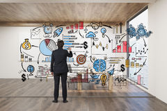 Businessman drawing on glassboard. Rear view of businessman drawing colorful startup sketch on glassboard in room with wooden floor and ceiling. 3d rendering Stock Photos