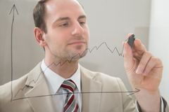 Businessman drawing a graph on a glass panel Royalty Free Stock Images