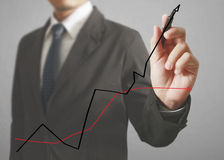 Businessman drawing graphics. A growing graph Royalty Free Stock Image