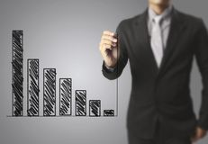 Businessman drawing graphics  growing graph. Businessman drawing graphics a growing graph Royalty Free Stock Photo