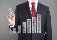 Businessman drawing a growing chart Stock Photos