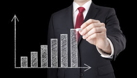 Businessman drawing a growing chart Royalty Free Stock Photos