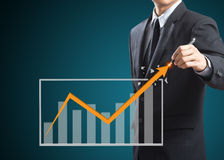 Businessman drawing a growth arrow Stock Image