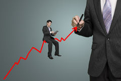 Businessman drawing growth red arrow and another sitting on it Stock Images