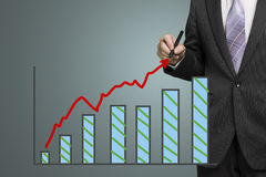 Businessman drawing growth red arrow and chart. In dark background Royalty Free Stock Images
