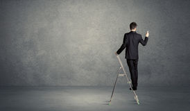 Businessman drawing on grunge wall. A man standing on ladder drawing with chalk in his hand on clear wall pattern background Stock Photos