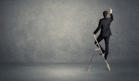 Businessman drawing on grunge wall. A man standing on ladder drawing with chalk in his hand on clear wall pattern background Stock Photo