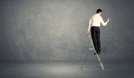Businessman drawing on grunge wall. A man standing on ladder drawing with chalk in his hand on clear wall pattern background Royalty Free Stock Photo