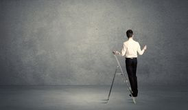 Businessman drawing on grunge wall. A man standing on ladder drawing with chalk in his hand on clear wall pattern background Stock Photography