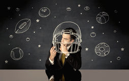 Businessman drawing helmet and sport balls Stock Images
