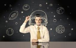 Businessman drawing helmet and sport balls Royalty Free Stock Photo
