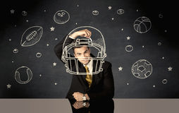 Businessman drawing helmet and sport balls Stock Photos