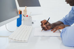 Businessman drawing at his desk Stock Photo
