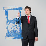 Businessman drawing hourglass Royalty Free Stock Photos