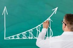 Businessman Drawing Increasing Dollar Graph Royalty Free Stock Photos