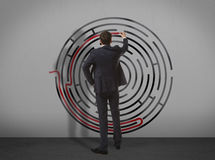 Businessman drawing labyrinth on wall Royalty Free Stock Image