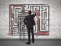 Businessman drawing labyrinth on wall Royalty Free Stock Photos