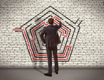 Businessman drawing labyrinth on wall Royalty Free Stock Photography