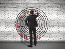 Businessman drawing labyrinth on wall Royalty Free Stock Images