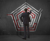 Businessman drawing labyrinth on wall Stock Photos