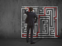 Businessman drawing labyrinth on wall Stock Photo