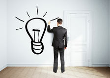 Businessman drawing lamp Royalty Free Stock Image