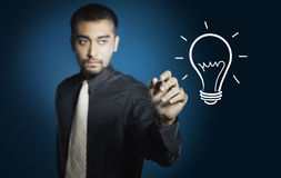 Businessman drawing light bulb Royalty Free Stock Photo