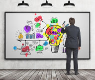 Businessman drawing light bulb sketch, whiteboard Royalty Free Stock Image