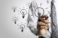 Businessman drawing light bulb Royalty Free Stock Images