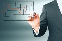 Businessman drawing maze solution. Businessman hand drawing maze sketch on gray background. Solution and achievement concept Stock Photo