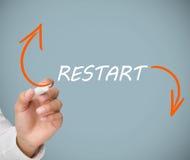 Businessman drawing orange arrows beside restart word. On grey background Royalty Free Stock Images
