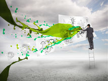 Businessman drawing on a paper next to green paint splash Stock Images