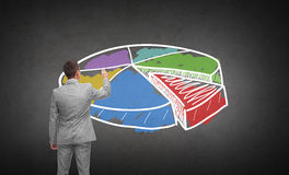 Businessman drawing pie chart from back. Business, people, advertisement , information and office concept - businessman drawing pie chart from back over dark Royalty Free Stock Photo