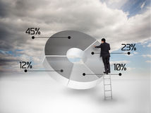 Businessman drawing a pie chart. With blue sky on the background Stock Image