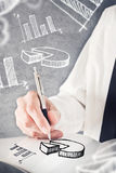 Businessman drawing pie chart and other infographics in note pad Stock Images