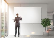 Businessman drawing at a poster in office. Rear view of a businessman writing at a blank poster hanging on a wooden office wall near a panoramic window. 3d Stock Images