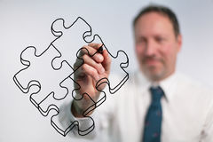 Businessman Drawing Puzzle Pieces. Businessman Drawing Outline Of Puzzle Pieces With Marker Royalty Free Stock Photography
