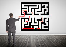 Businessman drawing a red line through qr code. In empty room royalty free stock photos