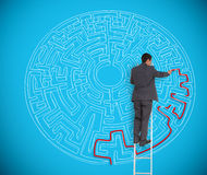 Businessman drawing red line to solve a complex maze. Businessman on ladder drawing red line to solve a complex maze on blue wall stock photography