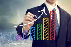 Businessman drawing a rising arrow stock image