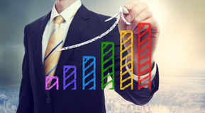 Businessman drawing a rising arrow over a bar graph. Above the city royalty free stock image