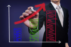 Businessman drawing a rising arrow over graph Royalty Free Stock Photography