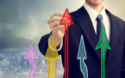Businessman drawing rising arrows. Businessman drawing the colorful rising arrows shapes royalty free stock photography