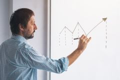 Businessman drawing rising linear diagram. Conceptual symbol for profit increase and success in business entrepreneurship royalty free stock images
