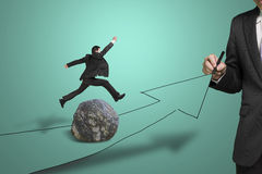 Businessman drawing road with arrow, another jumping over rock Stock Image